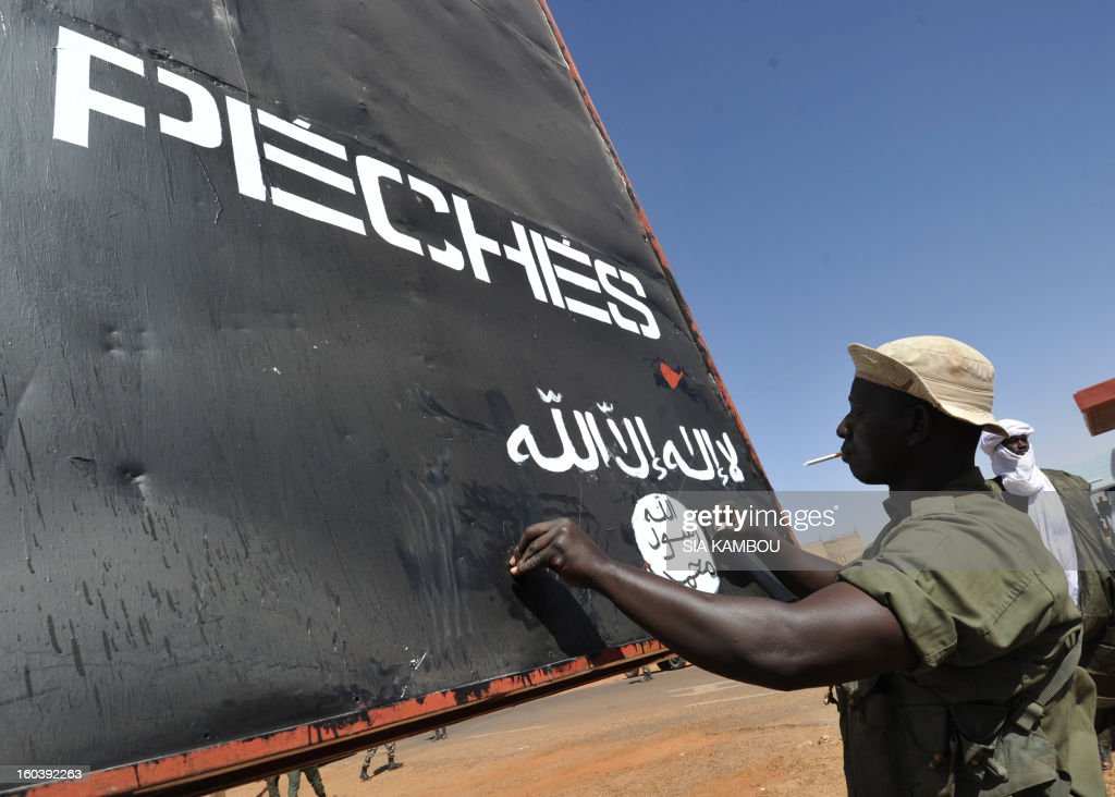 A Malian soldier covers on January 30, 2013 in the northern Malian city of Gao a billboard left by the Movement for Oneness and Jihad in West Africa (MUJAO), an offshoot of Al Qaeda in the Islamic Maghreb (AQIM). Gao was a key Islamist stronghold until it was retaken on January 26 by French and Malian troops in a major boost to the French-led offensive against the Al Qaeda-linked rebels, who have been holding Mali's vast desert north since last April. French troops on January 30 entered Kidal, the last Islamist bastion in Mali's north after a whirlwind Paris-led offensive, as France urged peace talks to douse ethnic tensions targeting Arabs and Tuaregs. Billboard reads: 'Al Hesbah, together for the pleasure of God almighty and the struggle against sins.'