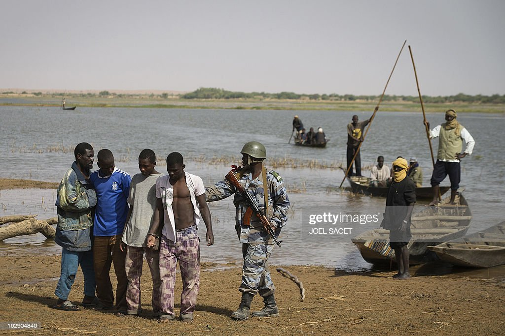 A Malian soldier (C) escorts prisoners after they arrived by boat in Kadji, on the Niger river on March 1, 2013. French and Malian troops launched an operation yesterday in the village of Kadji, northern Mali, where Islamists are hiding out on an island in the Niger river, a military source told AFP.