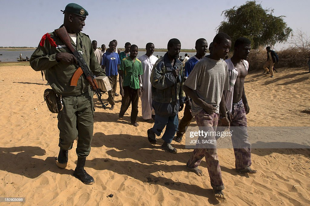 A Malian soldier (C) escorts prisoners after they arrived by boat in Kadji, on the Niger river on March 1, 2013. French and Malian troops launched an operation yesterday in the village of Kadji, northern Mali, where Islamists are hiding out on an island in the Niger river, a military source told AFP. AFP PHOTO / JOEL SAGET