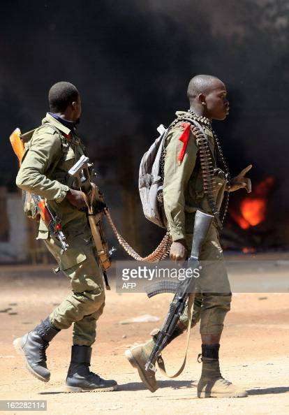 A Malian soldier gestures as he crosses with a comrade a street where they fight while clashes erupted in the city of Gao on February 21 2013 and an...