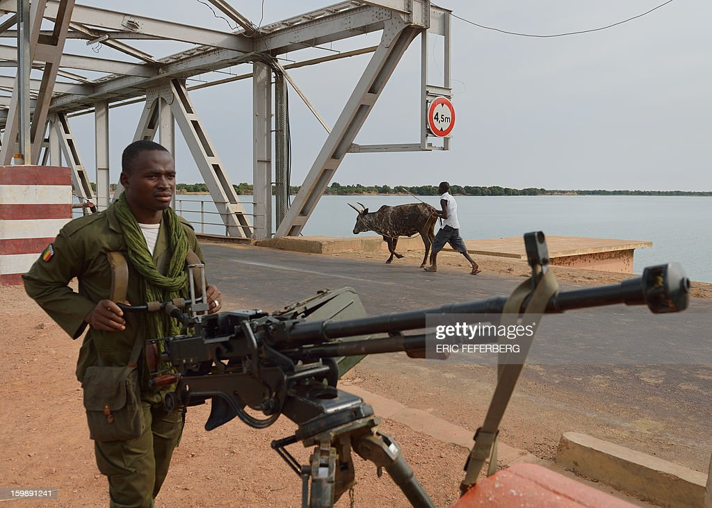 A Malian soldier holds a machine gun as he stands guard at the entrance of a strategic bridge over the Niger river on January 22, 2013, near Markala, some 270km north of Bamako. Mali's army chief today said his French-backed forces could reclaim the northern towns of Gao and fabled Timbuktu from Islamists in a month, as the United States began airlifting French troops to Mali.