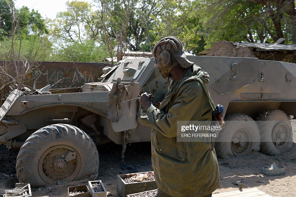 A Malian soldier inspects a Malian armoured vehicle and a stock of munitions on January 23, 2013 in the Malian barracks that was occupied by Islamists in Diabaly (400km north of Bamako), before a French air strike destroyed it . French soldiers destroyed the munitions that belonged to the Islamists to secure the town. AFP/PHOTO ERIC FEFERBERG
