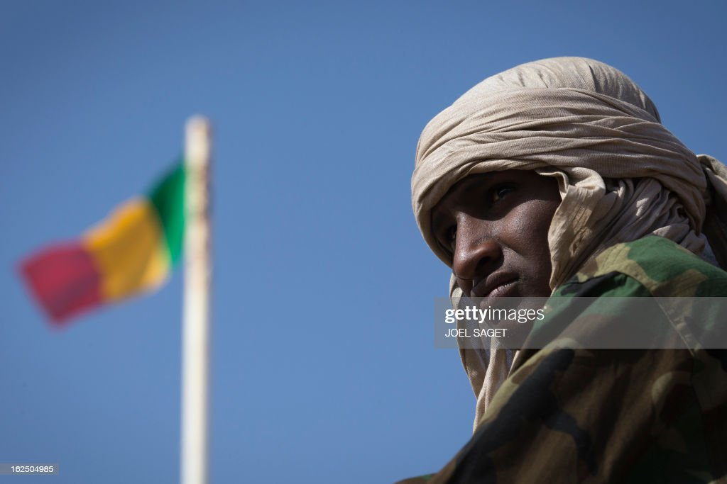 A Malian soldier is pictured next to a Malian flag in the centre of Gao on February 24, 2013. Tuareg militias battled Arab rebels in northern Mali Saturday, while French jets, US drones and Chad's elite desert forces were also in action in a major push to stamp out resistance from pockets of Islamist fighters. After recapturing the north's cities from the Al Qaeda groups that had controlled them since April 2012, the six-week-old French-led offensive took the fight to the retreating Islamist insurgents' toughest desert bastions.