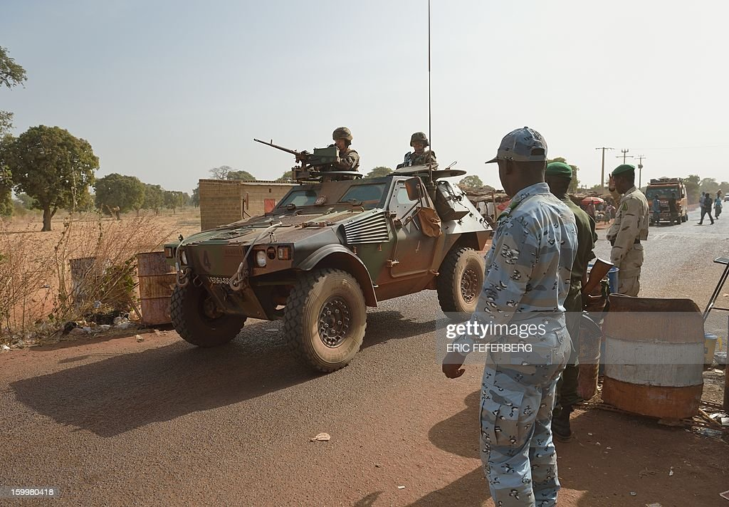 A Malian soldier looks at a French armoured vehicle part of a big convoy coming from Bamako and going to Daibali (400km north of Bamako) on January 24, 2013 in Segou. Paris sent in its forces on January 11 to rescue Mali from Al Qaeda-linked groups controlling the north.