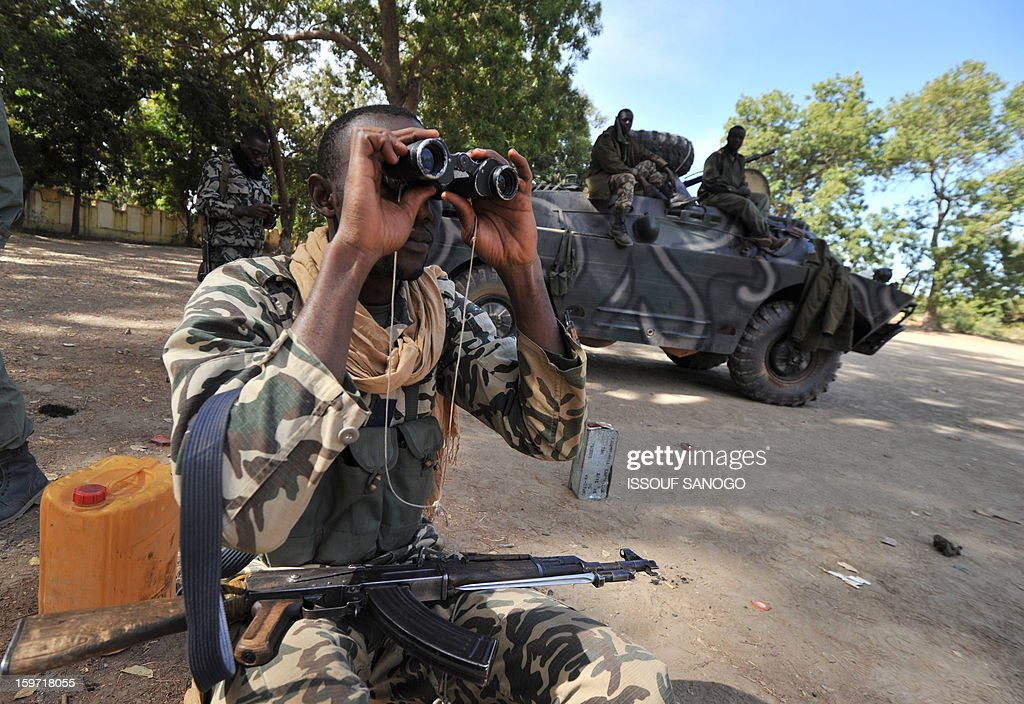 A Malian soldier looks through binoculars as others stand next to a military vehicule, on January 19, 2013, in city of Niono. Ivorian President Alassane Ouattara on January 19 called for a broader international commitment to the military operations in Mali, where Malian and French forces are battling Islamist militant groups that control the country's vast arid north. Some 2,000 members of MISMA (the International Mission for Mali Assistance), the African intervention force, are expected to be deployed by January 26. About 100 soldiers from Togo and Nigeria have already arrived in Bamako, and another 30 or so from Benin are en route to join them.