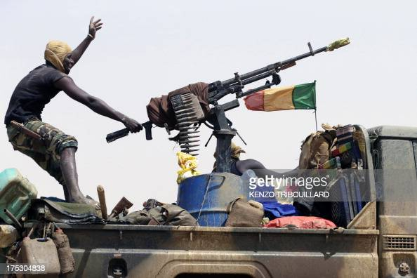 A Malian soldier patrolling on a road between Kidal and Gao gestures on a pickup truck on July 29 2013 in northern Mali one day after the vote for...