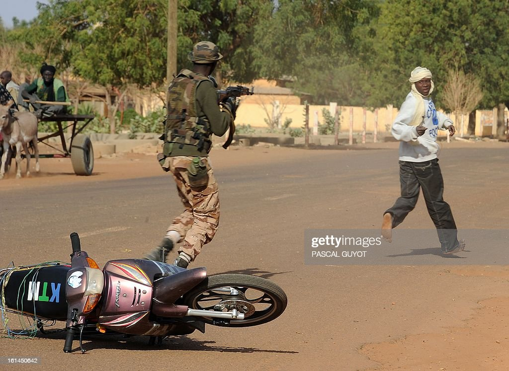 A Malian soldier points his machine gun at a man to arrest him at a checkpoint one day after Islamist gunmen battled French and Malian troops, on February 11, 2013 in Gao. AFP PHOTO / PASCAL GUYOT