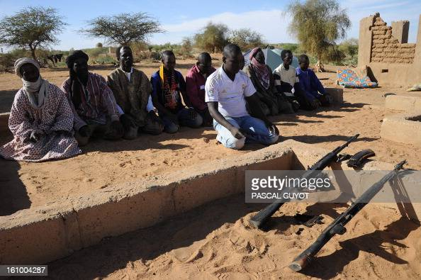 Malian soldier pray on February 8 2013 near the site where a suicide bomber blew himself up earlier in the day near a group of Malian soldiers in the...