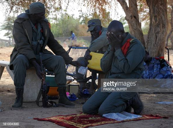 A Malian soldier prays on February 8 2013 near the site where a suicide bomber blew himself up earlier in the day near a group of Malian soldiers in...