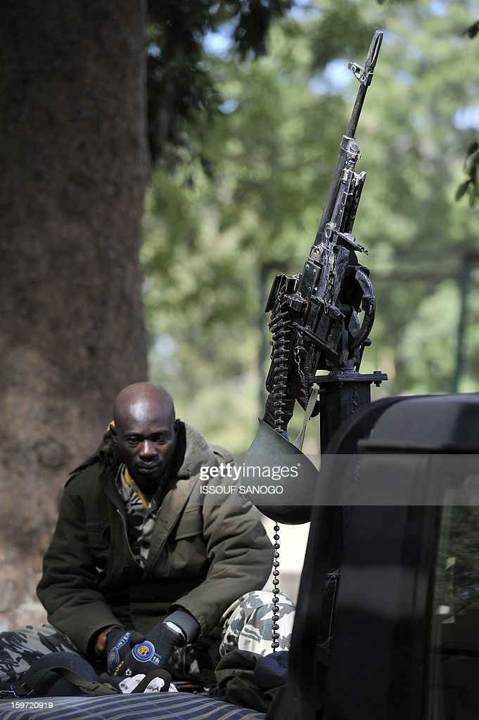 A Malian soldier rests at the back of a pickup truck mounted with a machine gun, on January 19, 2013, in city of Niono. Ivorian President Alassane Ouattara on January 19 called for a broader international commitment to the military operations in Mali, where Malian and French forces are battling Islamist militant groups that control the country's vast arid north. Some 2,000 members of MISMA (the International Mission for Mali Assistance), the African intervention force, are expected to be deployed by January 26. About 100 soldiers from Togo and Nigeria have already arrived in Bamako, and another 30 or so from Benin are en route to join them.