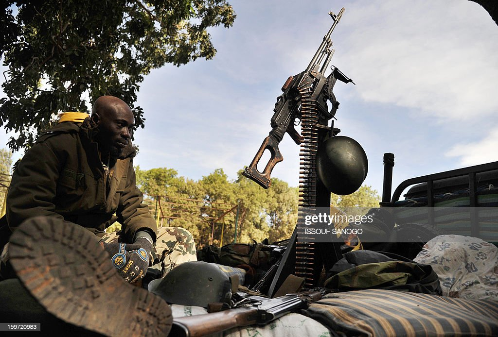 A Malian soldier rests at the back of a pickup truck mounted with a machine gun, on January 19, 2013, in city of Niono. Ivorian President Alassane Ouattara on January 19 called for a broader international commitment to the military operations in Mali, where Malian and French forces are battling Islamist militant groups that control the country's vast arid north. Some 2,000 members of MISMA (the International Mission for Mali Assistance), the African intervention force, are expected to be deployed by January 26. About 100 soldiers from Togo and Nigeria have already arrived in Bamako, and another 30 or so from Benin are en route to join them. AFP PHOTO / ISSOUF SANOGO