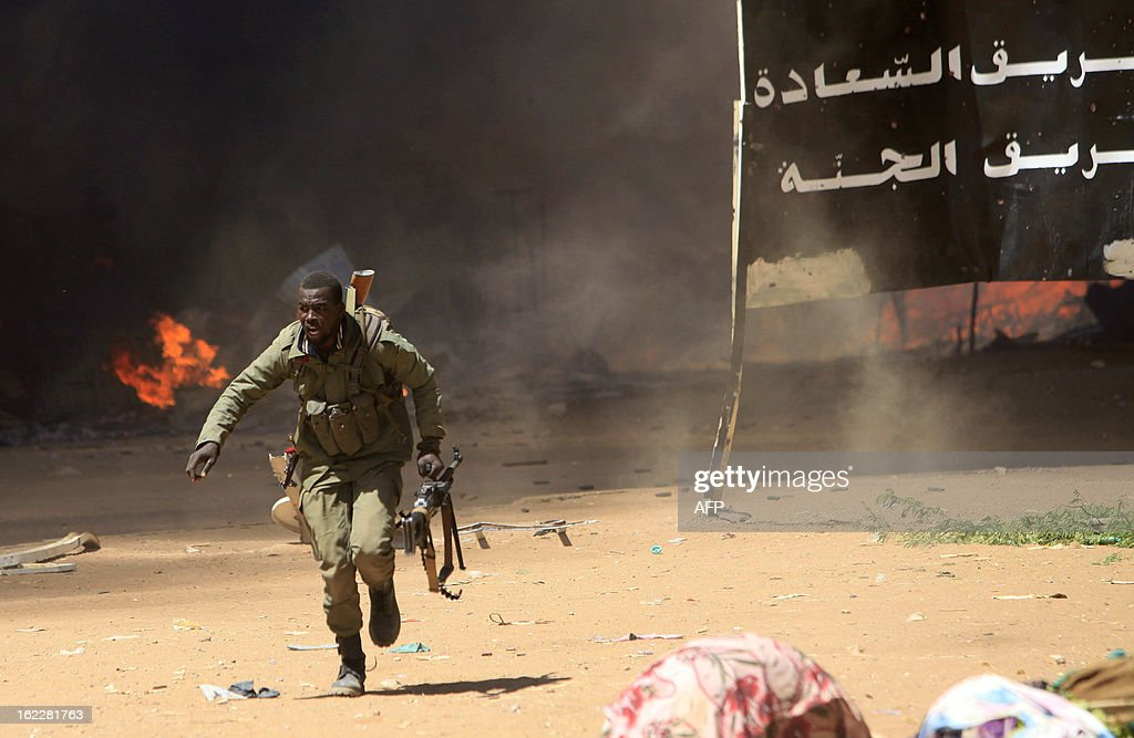 A Malian soldier runs for cover as he fights after clashes erupted in the city of Gao on February 21, 2013 and an apparent car bomb struck near a camp housing French troops as Malian and foreign forces struggled to secure Mali's volatile north against Islamist rebels.