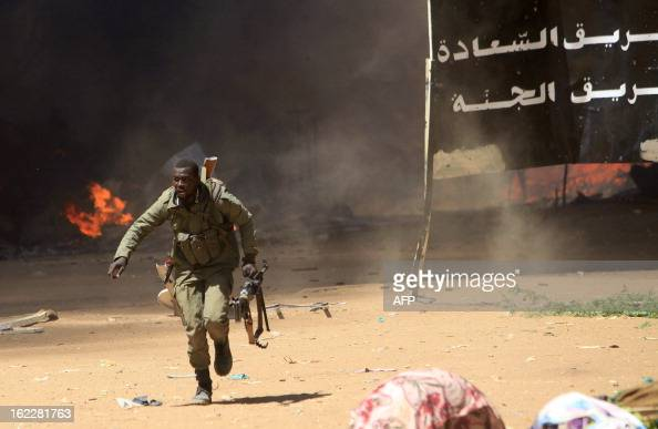 A Malian soldier runs for cover as he fights after clashes erupted in the city of Gao on February 21 2013 and an apparent car bomb struck near a camp...