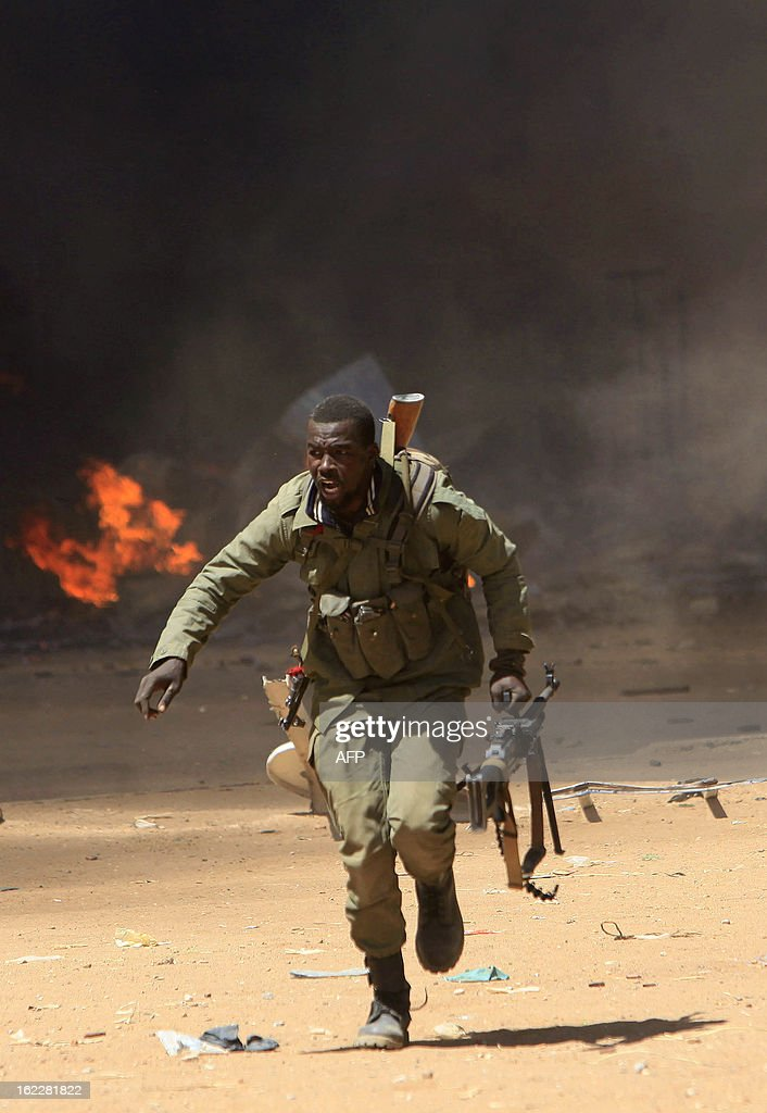 A Malian soldier runs for cover as he fights after clashes erupted in the city of Gao on February 21, 2013 and an apparent car bomb struck near a camp housing French troops as Malian and foreign forces struggled to secure Mali's volatile north against Islamist rebels. AFP PHOTO / FREDERIC LAFARGUE