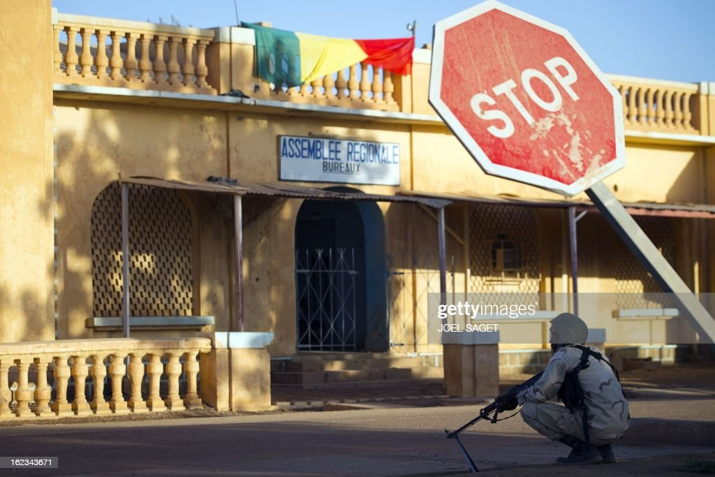 A Malian soldier sits in a street on February 22, 2013 in front of the offices of the Regional Assembly in central Gao, northern Mali. Five people, including two suicide bombers, died on February 22 in car bombings in northern Mali, a day after fierce urban battles between French-led forces and Islamists left up to 20 extremists dead, officials said.