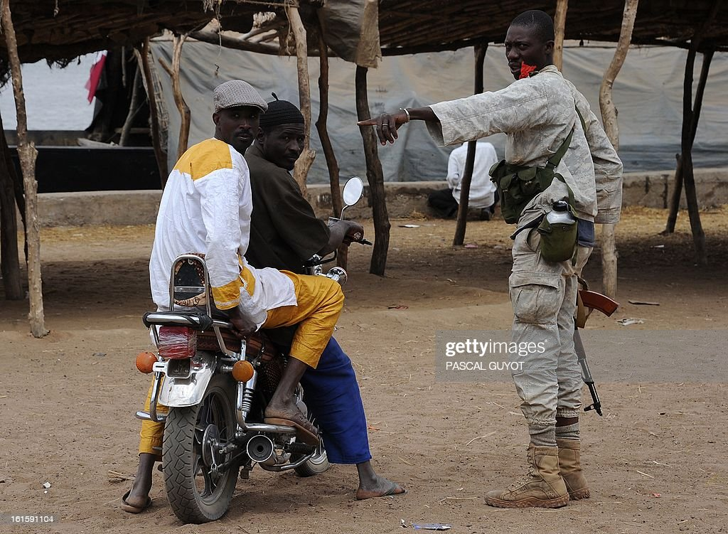 A Malian soldier speaks to youtsh as he patrols looking for Islamists on February 12, 2013 in the center of the northern Malian city of Gao, where the militant group Movement for Oneness and Jihad in West Africa (MUJAO) had controlled the city since June until the troops arrived in late January. African and French troops were on alert on February 12 after the MUJAO claimed a February 10 guerrilla attack and a pair of suicide bombings on February 8 and 9.