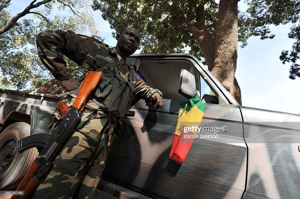 A Malian soldier stand guard near a pickup, on January 19, 2013, in city of Niono. Ivorian President Alassane Ouattara on January 19 called for a broader international commitment to the military operations in Mali, where Malian and French forces are battling Islamist militant groups that control the country's vast arid north. Some 2,000 members of MISMA (the International Mission for Mali Assistance), the African intervention force, are expected to be deployed by January 26. About 100 soldiers from Togo and Nigeria have already arrived in Bamako, and another 30 or so from Benin are en route to join them.. AFP / PHOTO / ISSOUF