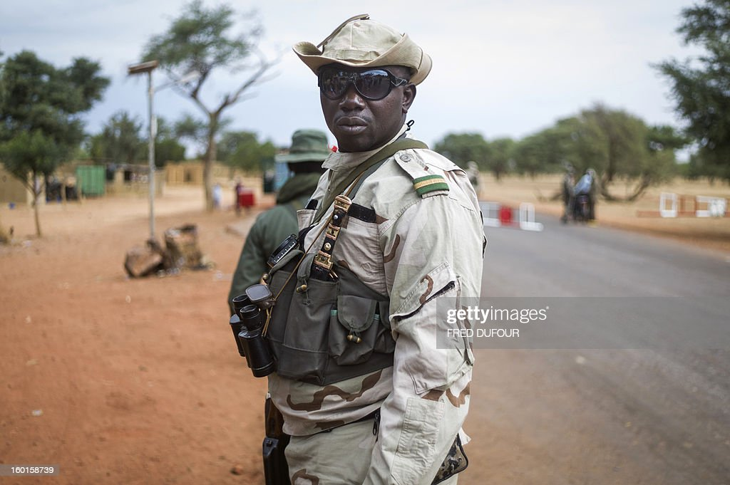 A Malian soldier stands at a checkpoint near Sevare on January 27, 2013. French-led troops were advancing on Mali's fabled desert city of Timbuktu on Sunday after capturing a string of other towns in their offensive against Islamist militant groups in the north of the country. Meanwhile, African leaders meeting in the Ethiopian capital were discussing scaling up the number of African troops to join the offensive, after the African Union's outgoing chief admitted the body had not done enough to help Mali. AFP PHOTO / FRED DUFOUR