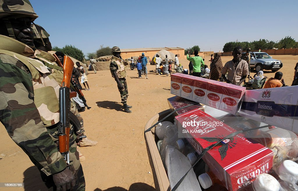 A malian soldier stands by a street vendor selling tobacco, which was forbidden during the islamist occupation, on February 3, 2013 in Gao. France said it carried out major air strikes today near Kidal, the last bastion of armed extremists chased from Mali's desert north in a lightning French-led offensive.