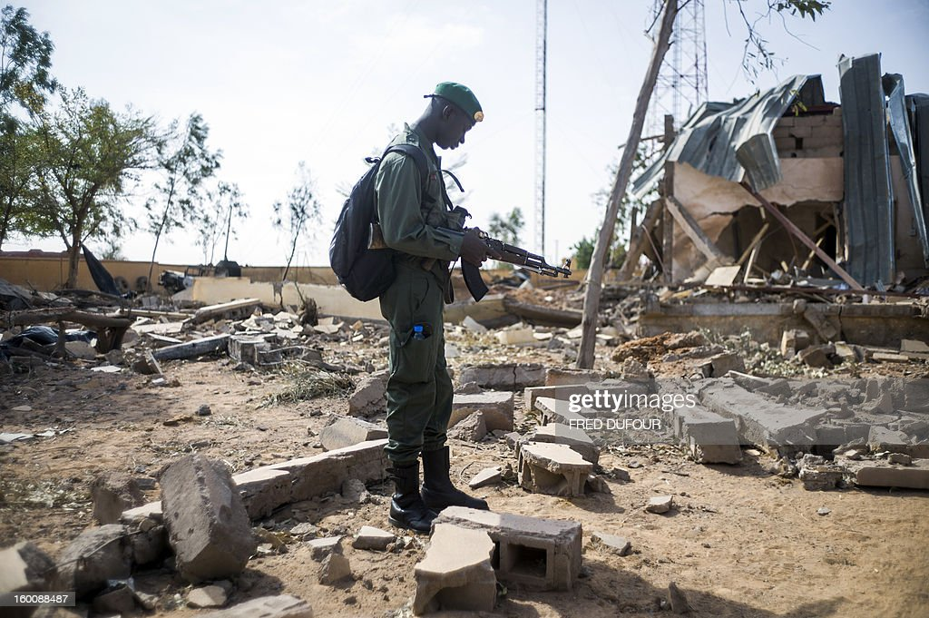 A Malian soldier stands in a destroyed area on January 26, 2013 in the key central town of Konna controled by French and Malian army since last week after being taken last January 11 by Islamist groups. French and Malian troops pushed north towards the key Islamist strongholds in northern Mali today, as west African defence chiefs gathered in Ivory Coast to review plans to deploy a regional intervention force. AFP PHOTO / FRED DUFOUR