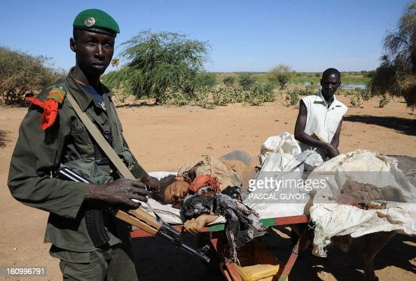 A Malian soldier stands next to a man carrying on a cart on February 8 2013 the corpse of a suicide bomber who blew himself up near a group of Malian...