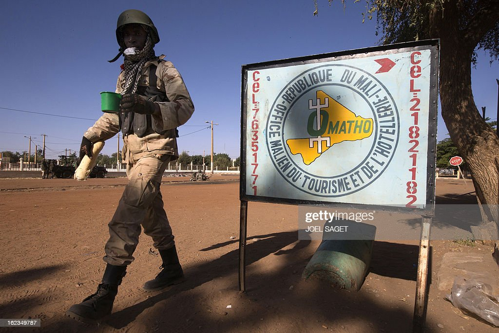 A Malian soldier walks on February 22, 2013 in the centre of northern Mali's largest city of Gao. Five people, including two suicide bombers, died on February 22 in car bombings in northern Mali, a day after fierce urban battles between French-led forces and Islamists left up to 20 extremists dead, officials said. AFP PHOTO /JOEL SAGET
