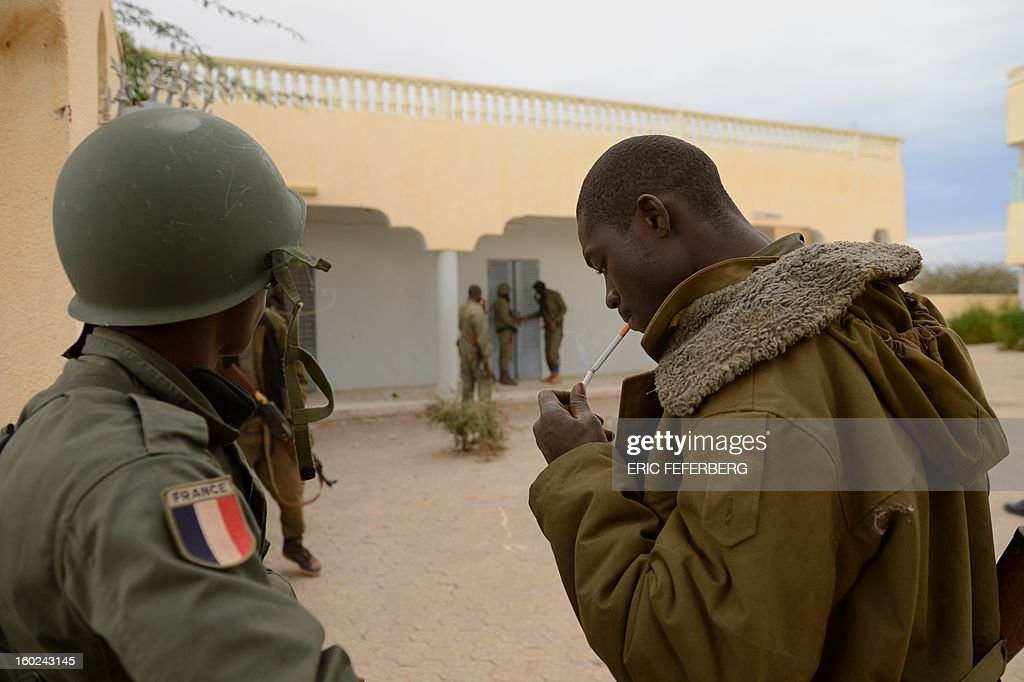 A Malian soldier with a French flag insignia watches soldiers entering a house which was held by Islamists after Malian and French soldiers entered the historic city of Timbuktu, occupied for 10 months by Islamists who imposed a harsh form of sharia, on January 28, 2013. Residents of the ancient city on the edge of the Sahara desert erupted in joy as the French-led troops entered the town, jubilantly waving French and Malian flags after months of suffering under the Islamists' brutal rule. AFP PHOTO / ERIC FEFERBERG