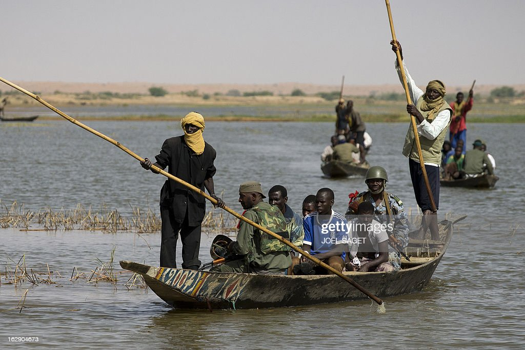 Malian soldiers arrive by boat with prisoners in Kadji, on the Niger river on March 1, 2013. French and Malian troops launched an operation yesterday in the village of Kadji, northern Mali, where Islamists are hiding out on an island in the Niger river, a military source told AFP.