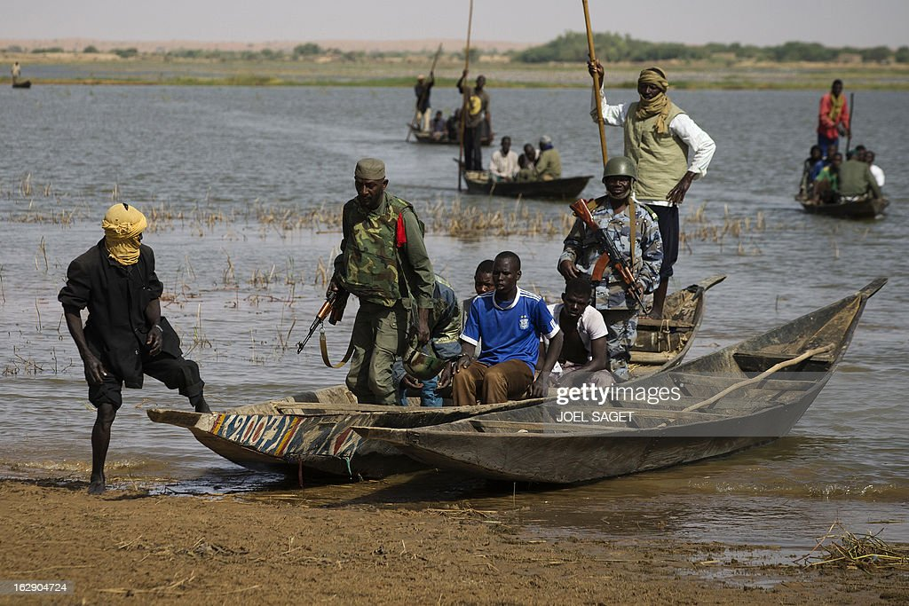 Malian soldiers arrive with prisoners on a boat in Kadji, on the Niger river on March 1, 2013. French and Malian troops launched an operation yesterday in the village of Kadji, northern Mali, where Islamists are hiding out on an island in the Niger river, a military source told AFP.