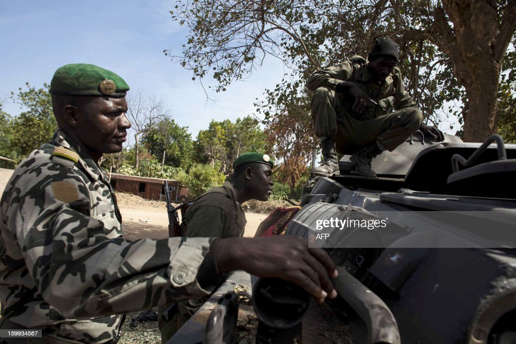 Malian soldiers controls a tanks destroyed by French shellings on January 23, 2013 in Diabaly, which was seized last week by Islamists and then heavily bombed by French planes. The regional bloc, the Economic Community of West African States (ECOWAS), has pledged up to 4,000 troops to join a French-led intervention force to stop the advance of Islamist rebels based in northern Mali. AFP PHOTO / FABIO BUCCIARELLI
