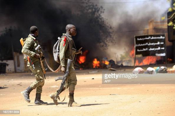 Malian soldiers cross a street as they fight while clashes erupted in the city of Gao on February 21 2013 and an apparent car bomb struck near a camp...