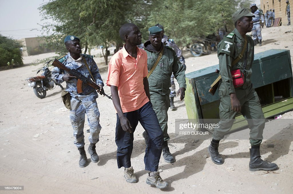 Malian soldiers escort a man (C), arrested on suspicion of being an informator of islamists rebels, during a patrol in a street of Timbuktu on February 1, 2013, as French-led troops worked today to secure the last Islamist stronghold in the north after a lightning offensive against the extremists. The fabled desert city of Timbuktu, an ancient centre of Islamic learning, has been recaptured on January 28 by French-led forces in their offensive against Islamist rebels who have been occupying Mali's north since last April. AFP PHOTO / FRED DUFOUR
