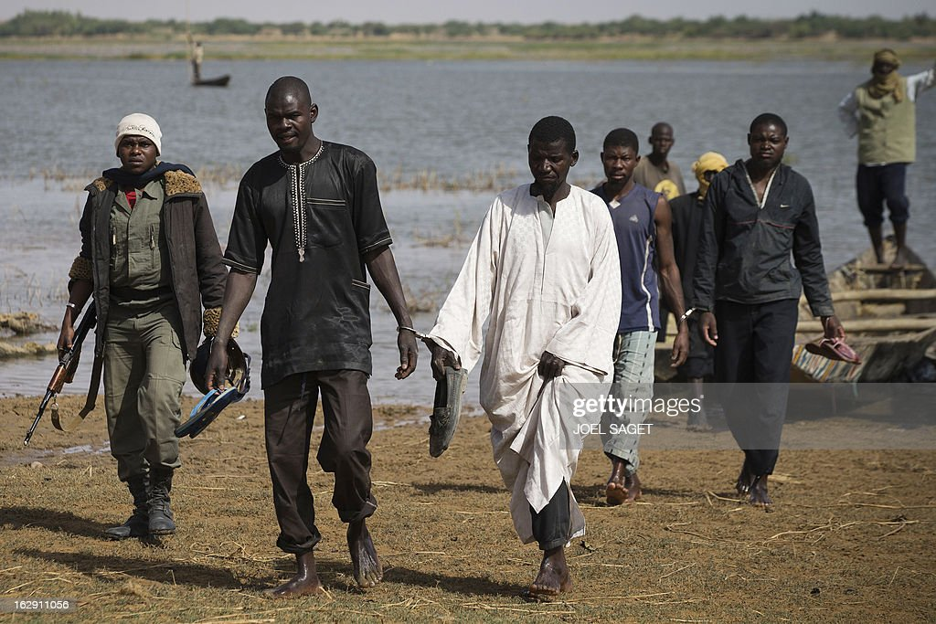 Malian soldiers escort prisoners after they arrived by boat in Kadji, on the Niger river on March 1, 2013. French and Malian troops launched an operation yesterday in the village of Kadji, northern Mali, where Islamists are hiding out on an island in the Niger river, a military source told AFP.