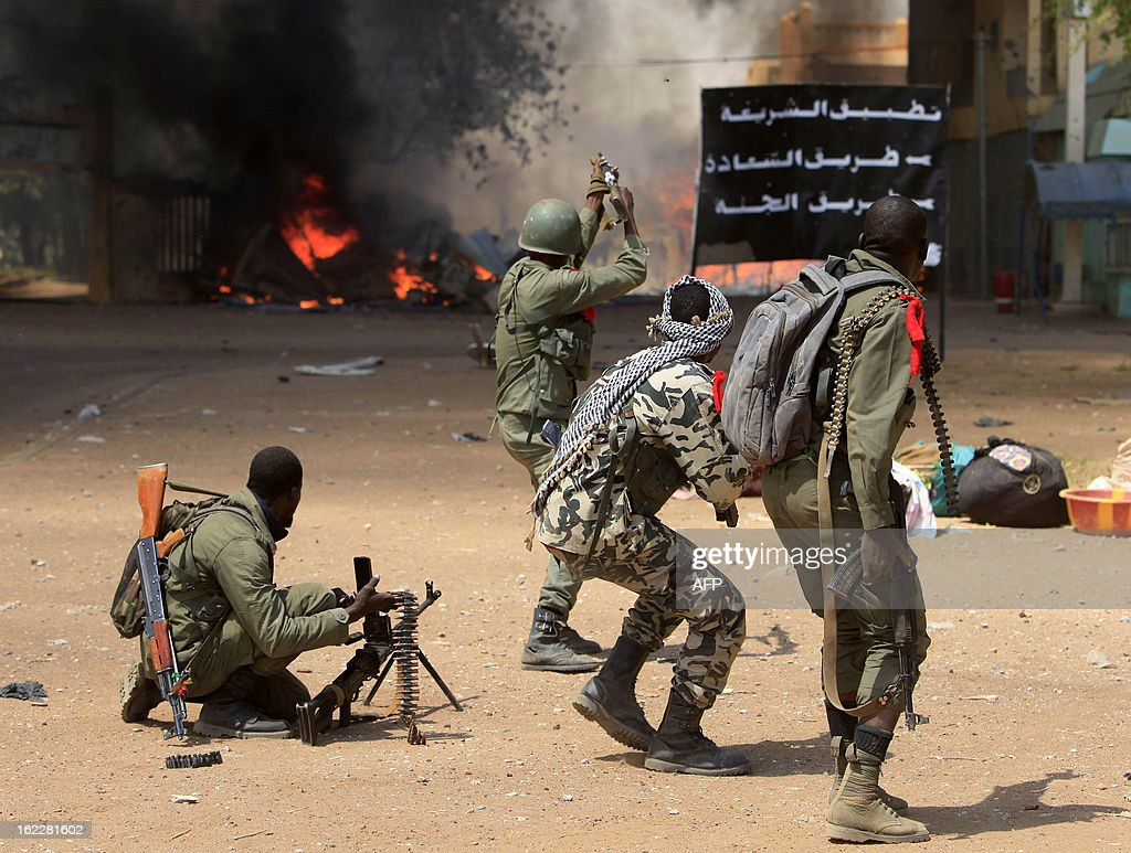 Malian soldiers fight while clashes erupted in the city of Gao on February 21, 2013 and an apparent car bomb struck near a camp housing French troops as Malian and foreign forces struggled to secure Mali's volatile north against Islamist rebels. AFP PHOTO / FREDERIC LAFARGUE