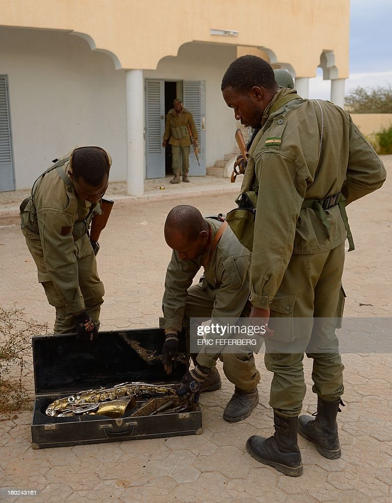 Malian soldiers find ammunition in a saxophone box after searching a house which was held by Islamists in the historic city of Timbuktu on January 28, 2013. French-led forces today seized Mali's fabled desert city of Timbuktu in a lightning advance north as fleeing Islamists torched a building housing priceless ancient manuscripts. Residents of the ancient city on the edge of the Sahara desert erupted in joy as the French-led troops entered the town, jubilantly waving French and Malian flags after months of suffering under the Islamists' brutal rule.