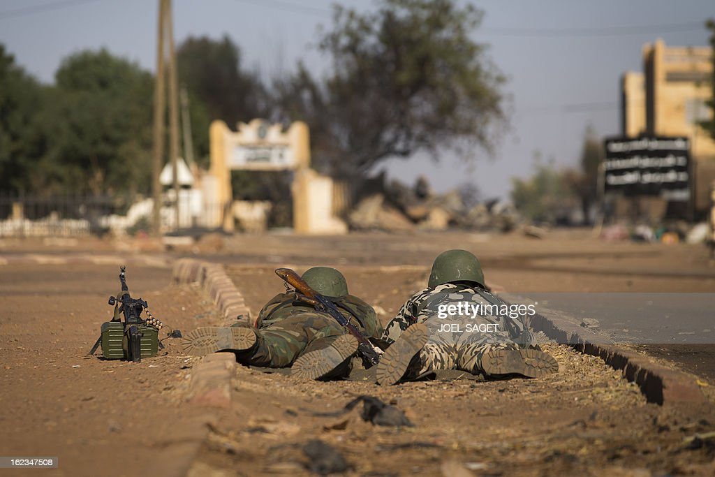 Malian soldiers lay on the floor as they survey a street on February 22, 2013 in Gao, northern Mali. Five people, including two suicide bombers, died on February 22 in car bombings in northern Mali, a day after fierce urban battles between French-led forces and Islamists left up to 20 extremists dead, officials said.