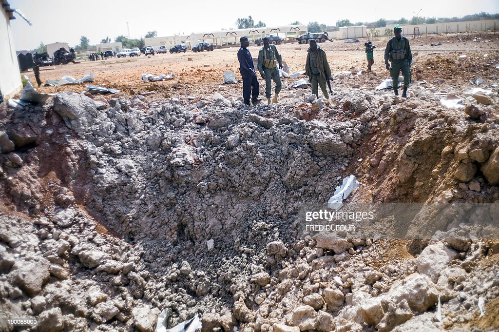 Malian soldiers lead journalists to a 'crater' in a destroyed area of Konna on January 26, 2013. French-led forces today wrested control of the airport at the Islamist stronghold of Gao, 1,200 kilometres (750 miles) northeast of the Mali capital Bamako, a security source said.
