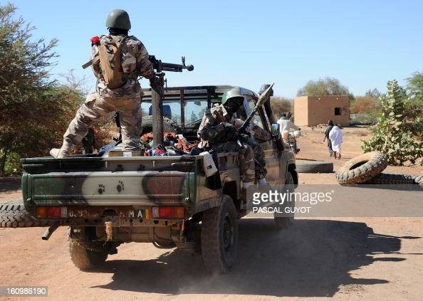 Malian soldiers on a pickup truck drive toward a Malian Army checkpoint on February 8 2013 at the site where a suicide bomber blew himself up earlier...