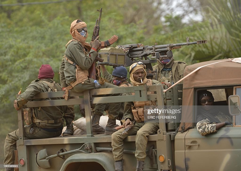 Malian soldiers patrol aboard a vehicule mounted with a machine gun in a street of Diabaly (400km north of the capital Bamako) on January 26, 2013. French-led Malian troops recaptured the Islamist stronghold of Gao, today, the biggest town in northern Mali, and troops from Niger and Chad 'will now take up the baton,' the French defence ministry said.