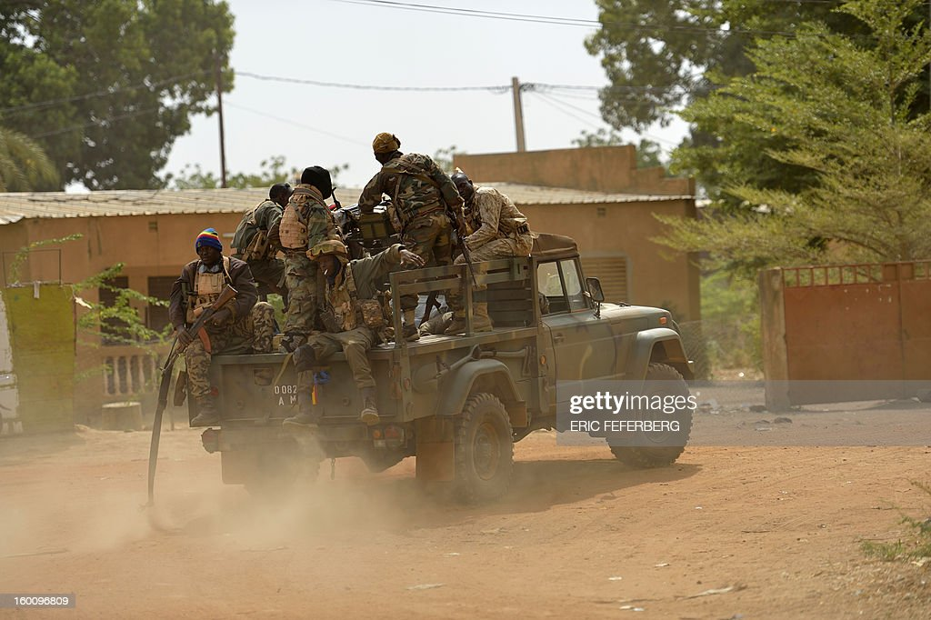 Malian soldiers patrol in a street of Diabaly (400km north of the capital Bamako) on January 26, 2013. French-led Malian troops recaptured the Islamist stronghold of Gao, today, the biggest town in northern Mali, and troops from Niger and Chad 'will now take up the baton,' the French defence ministry said.