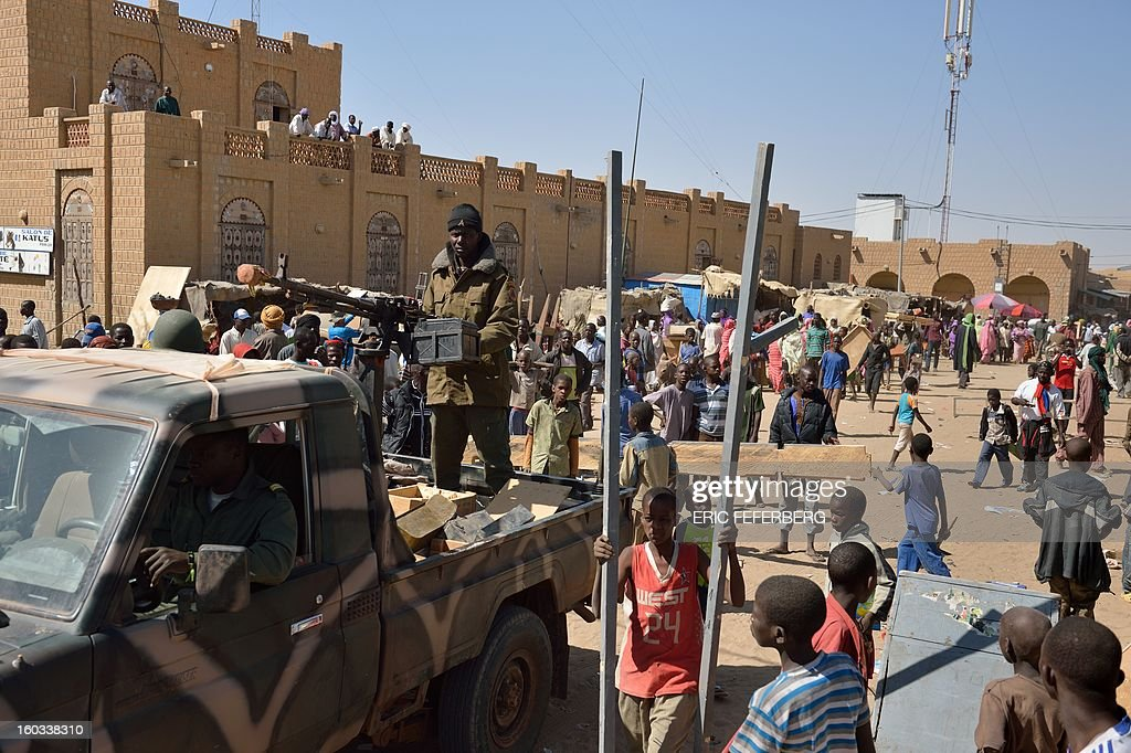 Malian soldiers patrol on a pick-up truck to keep looters at bay on January 29, 2013 in Timbuktu after French-led troops freed the northern desert city on January 28 from Islamist control. Hundreds of Malians looted Arab-owned shops on January 29 in Timbuktu as global donors pledged over 455 million US dollars (340 million euro) at a donor conference in the Ethiopian capital Addis Ababa for military operations in Mali and humanitarian aid to rout the radicals from the north. Sign reads 'The city of Timbuktu is founded on Islam and will be judged only by the Islamic law (sharia)). AFP PHOTO / ERIC FEFERBERG CAPTION CORRECTION