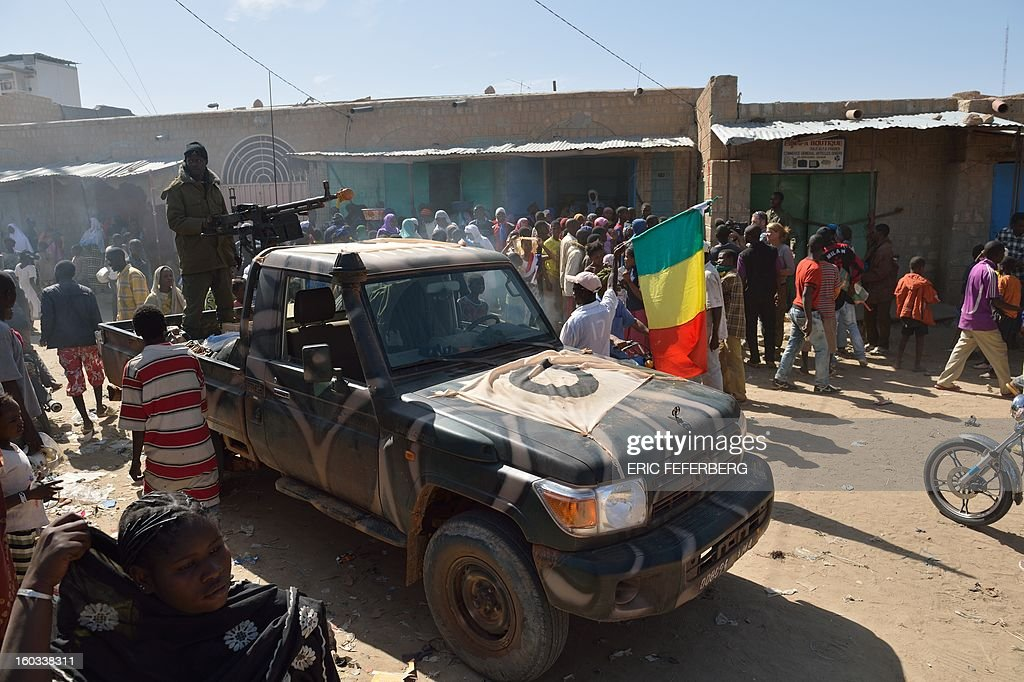 Malian soldiers patrol on a pick-up truck to keep looters at bay on January 29, 2013 in Timbuktu after French-led troops freed the northern desert city on January 28 from Islamist control. Hundreds of Malians looted Arab-owned shops on January 29 in Timbuktu as global donors pledged over 455 million US dollars (340 million euro) at a donor conference in the Ethiopian capital Addis Ababa for military operations in Mali and humanitarian aid to rout the radicals from the north. Sign reads 'The city of Timbuktu is founded on Islam and will be judged only by the Islamic law (sharia)). AFP PHOTO / ERIC FEFERBERG