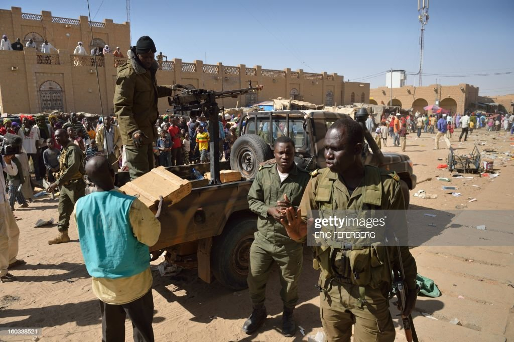 Malian soldiers recover ammunitions as they patrol on a pick-up truck to keep looters at bay on January 29, 2013 in Timbuktu after French-led troops freed the northern desert city on January 28 from Islamist control. Hundreds of Malians looted Arab-owned shops on January 29 in Timbuktu as global donors pledged over 455 million US dollars (340 million euro) at a donor conference in the Ethiopian capital Addis Ababa for military operations in Mali and humanitarian aid to rout the radicals from the north. Sign reads 'The city of Timbuktu is founded on Islam and will be judged only by the Islamic law (sharia)).