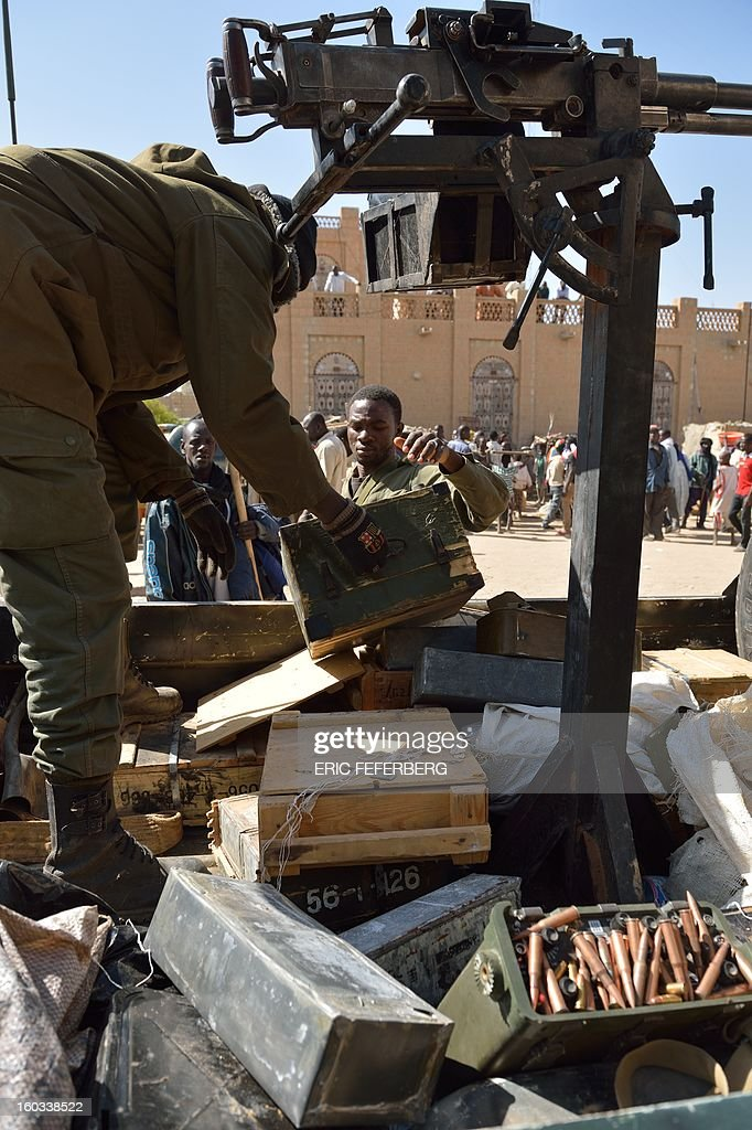 Malian soldiers recover ammunitions from a shop as they patrol on a pick-up truck to keep looters at bay on January 29, 2013 in Timbuktu after French-led troops freed the northern desert city on January 28 from Islamist control. Hundreds of Malians looted Arab-owned shops on January 29 in Timbuktu as global donors pledged over 455 million US dollars (340 million euro) at a donor conference in the Ethiopian capital Addis Ababa for military operations in Mali and humanitarian aid to rout the radicals from the north. Sign reads 'The city of Timbuktu is founded on Islam and will be judged only by the Islamic law (sharia)). AFP PHOTO / ERIC FEFERBERG