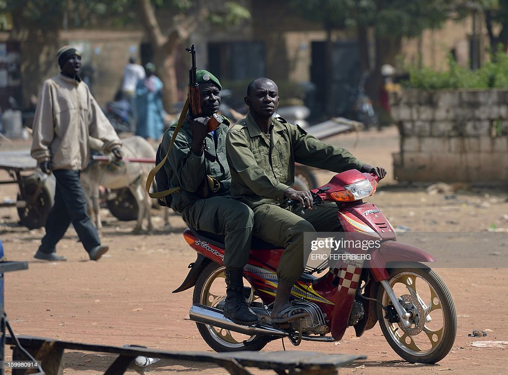 Malian soldiers ride a motocycle in a street of Merkala, on January 24, 2013. The first of the 6,000 troops pledged by African nations to support France started heading north, moving closer to the areas a trio of Al Qaeda-linked groups seized in April in the chaotic aftermath of a coup in Bamako.