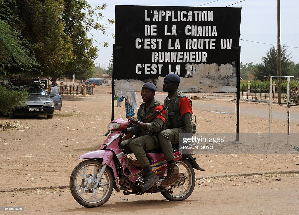 Malian soldiers ride a motorcycle as they look for Islamists on February 12, 2013 in the center of the northern Malian city of Gao, where the militant group Movement for Oneness and Jihad in West Africa (MUJAO) had controlled the city since June until the troops arrived in late January. African and French troops were on alert on February 12 after the MUJAO claimed a February 10 guerrilla attack and a pair of suicide bombings on February 8 and 9. Billboard reads: 'Enforcement of Sharia is the road to happiness.'