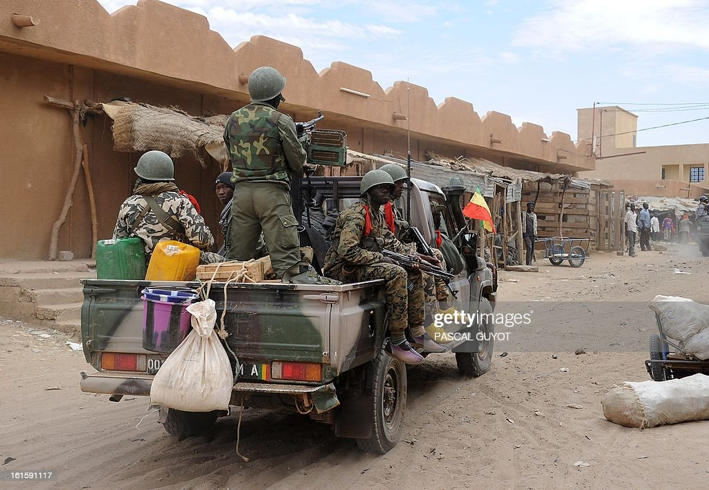 Malian soldiers ride a pickup truck as they look for Islamists on February 12, 2013 in the center of the northern Malian city of Gao, where the militant group Movement for Oneness and Jihad in West Africa (MUJAO) had controlled the city since June until the troops arrived in late January. African and French troops were on alert on February 12 after the MUJAO claimed a February 10 guerrilla attack and a pair of suicide bombings on February 8 and 9.