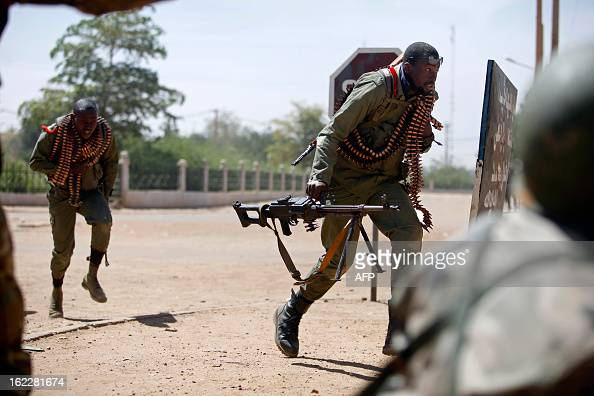 Malian soldiers run for cover as they fight after clashes erupted in the city of Gao on February 21 2013 and an apparent car bomb struck near a camp...