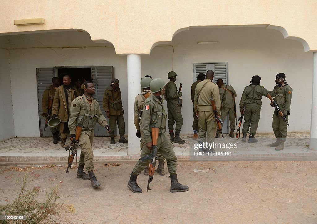Malian soldiers search a house which was held by Islamists in the historic city of Timbuktu on January 28, 2013. French-led forces today seized Mali's fabled desert city of Timbuktu in a lightning advance north as fleeing Islamists torched a building housing priceless ancient manuscripts. Residents of the ancient city on the edge of the Sahara desert erupted in joy as the French-led troops entered the town, jubilantly waving French and Malian flags after months of suffering under the Islamists' brutal rule. AFP PHOTO / ERIC FEFERBERG