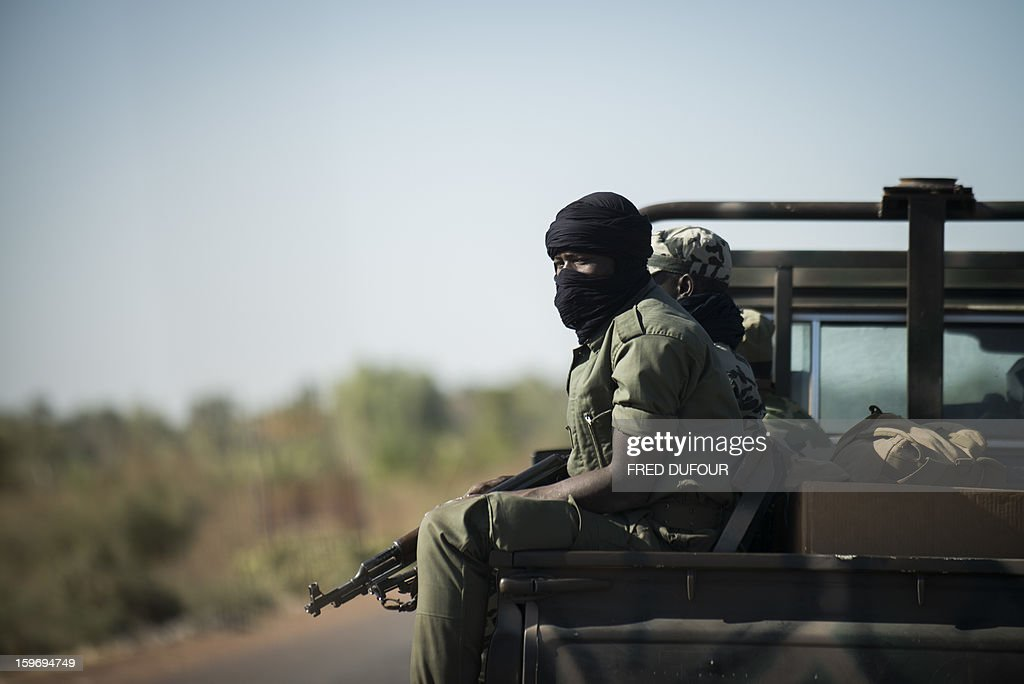 Malian soldiers sit in a pick up on their way to Niono, 340km north from Bamako, on January 18, 2013 in Markala. France confirmed today that Malian troops had taken control of the key central town of Konna from armed Islamists who seized the country's vast desert north in April last year.AFP PHOTO / FRED DUFOUR